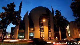 An dem Neubau der Moschee in Köln fahren am Donnerstag (09.08.2012) im Abendlicht Autos vorbei.Foto: Oliver Berg dpa/lnw