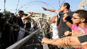 Egyptian security forces (L) face anti Muslim Brotherhood protesters