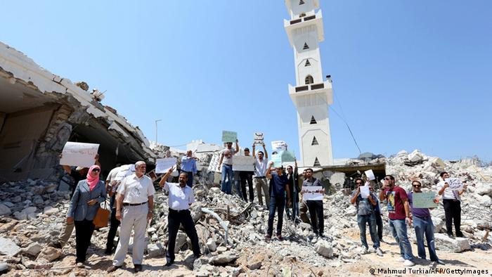 Libyan protesters holding placards stand on the rubble of the destroyed in Tripoli. AFP PHOTO/MAHMUD TURKIA
