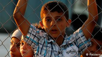 New Syrian refugee children look out from behind a fence as they arrive at a stopover facility REUTERS/Umit Bektas)