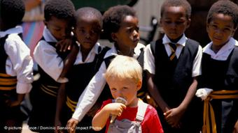 Black school children with a white boy eating an ice cream cone in front of them, Johannesburg, South Africa.
