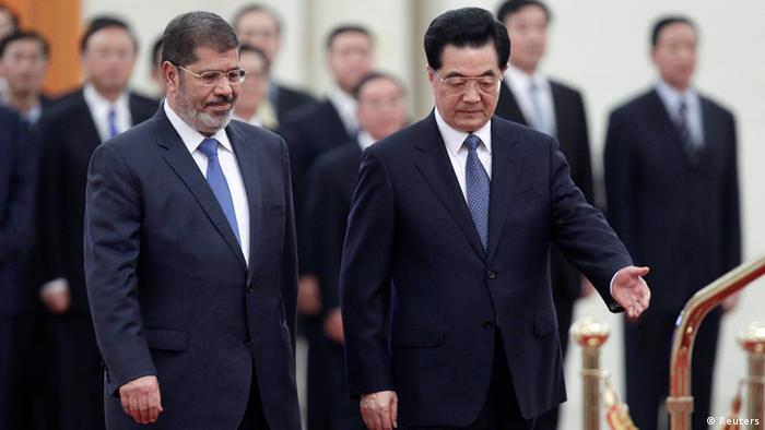 China's President Hu Jintao (R) shows the way for his Egyptian counterpart Mohamed Mursi during an official welcoming ceremony at the Great Hall of the People in Beijing August 28, 2012. REUTERS/Jason Lee (CHINA - Tags: POLITICS)
