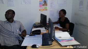 Two people sitting at their desks at the Hei Julor call center Photo: Isaac Kaledzi, August 2012, in Accra, Ghana