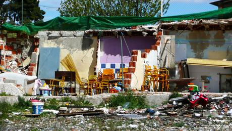 Rubble and chairs stand next to the concrete walls of buildings half standing in Canada Real, a slum just outside of Madrid. Photo: Lauren Frayer