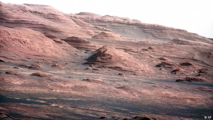In this image released by NASA on Monday, Aug. 27, 2012, a chapter of the layered geological history of Mars is laid bare in this color image from NASA's Curiosity rover showing the base of Mount Sharp, the rover's eventual science destination. The image is a portion of a larger image taken by Curiosity's 100-millimeter Mast Camera on Aug. 23, 2012. Scientists enhanced the color in one version to show the Martian scene under the lighting conditions we have on Earth, which helps in analyzing the terrain. The pointy mound in the center of the image, looming above the rover-sized rock, is about 1,000 feet (300 meters) across and 300 feet (100 meters) high. (Foto:NASA/JPL-Caltech/MSSS/AP/dapd)