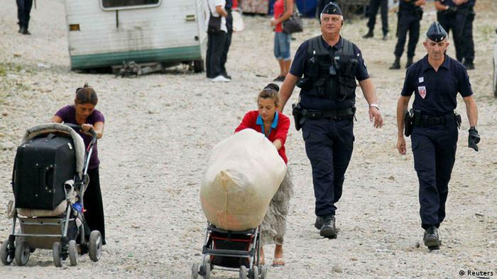 French CRS police evacuate families and remove their caravans from an illegal camp housing about 114 Roma