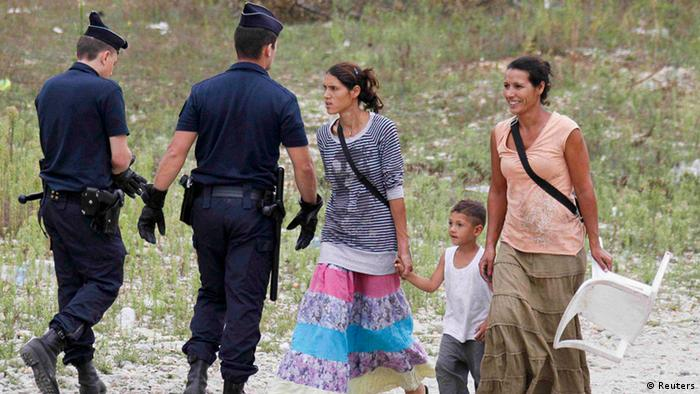 French CRS police officers evacuate families from an illegal camp housing about 114 Roma, referred to as Gens du Voyage, in Saint-Priest, near Lyon, southeastern France, August 28, 2012. The French Interior minister said on Monday he would ask Romania and Bulgaria to do more to integrate their Roma minorities as the new government in Paris grapples with how to handle Roma immigrants in France. REUTERS/Robert Pratta (FRANCE - Tags: SOCIETY IMMIGRATION POLITICS)