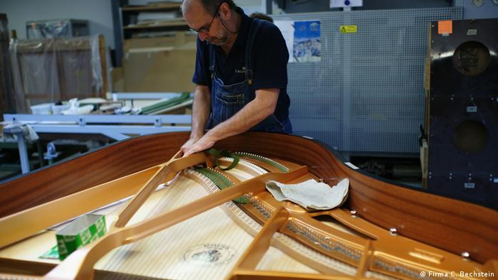 Michael Stiasny, a piano producer at C. Bechstein working on the internal parts of a piano.