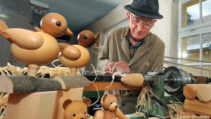 Der 74-jährige Drechslermeister Klaus Weber steht an der Drechselbank in seiner Werkstatt in Seiffen in Sachsen und fertigt hölzerne Vögel und Bären (Foto: Wolfgang Thieme/dpa)