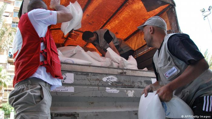 Syrian Red Crescent staff unload sacks of food in Damascus. STR/AFP/GettyImages)
