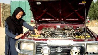 Eine afghanische Frau schaut unter die offene Motorhaube eines Autos (Foto: DW/Abu Jamal)