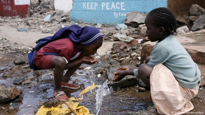 Children from Kibera, Africa's most populous slum, drink water from a broken pipe in front of a building