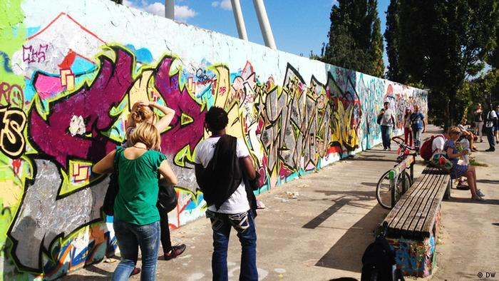 People walking in front of graffiti-laden wall at Mauerpark Berlin (DW)