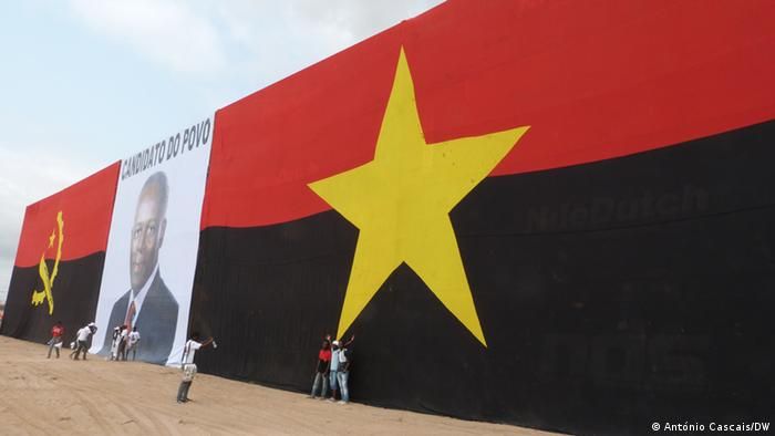 Photo shows a giant Angolan flag with a large poster of dos Santos hanging in front of it