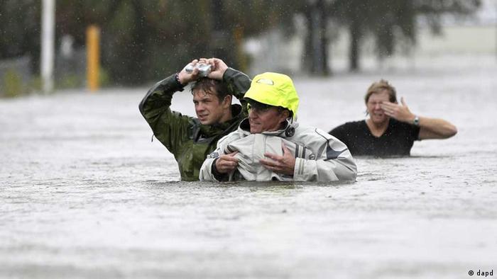 Eine Familie watet durch die Fluten (Foto: dapd)
