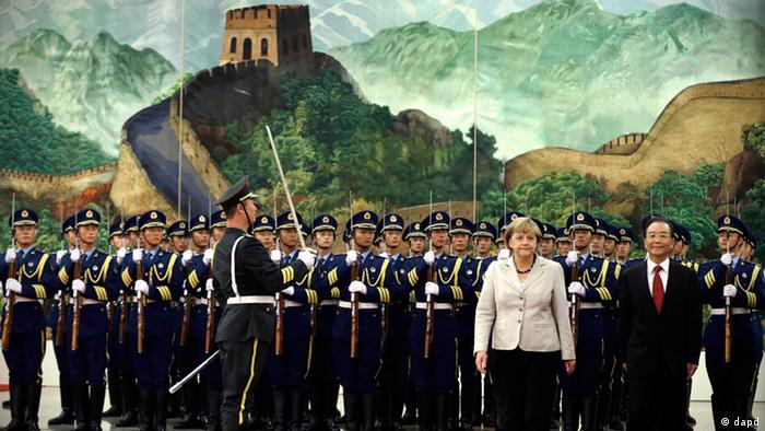 German Chancellor Angela Merkel, second from right on red carpet, and and Chinese Premier Wen Jiabao, right, walk together after inspecting a guard of honor during a welcome ceremony held at the Great hall of the People in Beijing Thursday, Aug. 30, 2012. (AP Photo/Ng Han Guan)