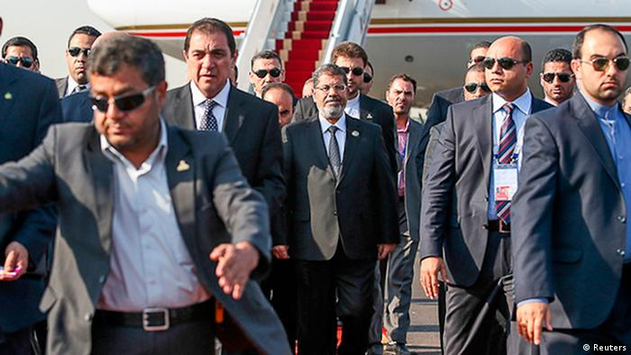 Egypt's President Mohamed Mursi (C) arrives in Mehrabad airport in Tehran ahead of the 16th summit of the Non-Aligned Movement, August 30, 2012. Mursi arrived in Tehran on Thursday, the first Egyptian leader to visit Iran since its Islamic revolution in 1979. REUTERS/Roohollah Vahdati/ISNA (IRAN - Tags: POLITICS) FOR EDITORIAL USE ONLY. NOT FOR SALE FOR MARKETING OR ADVERTISING CAMPAIGNS. THIS IMAGE HAS BEEN SUPPLIED BY A THIRD PARTY. IT IS DISTRIBUTED, EXACTLY AS RECEIVED BY REUTERS, AS A SERVICE TO CLIENTS