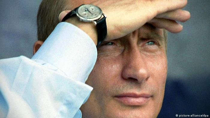 Putin shields his eyes with a hand and looks into the distance. (picture-alliance/dpa)