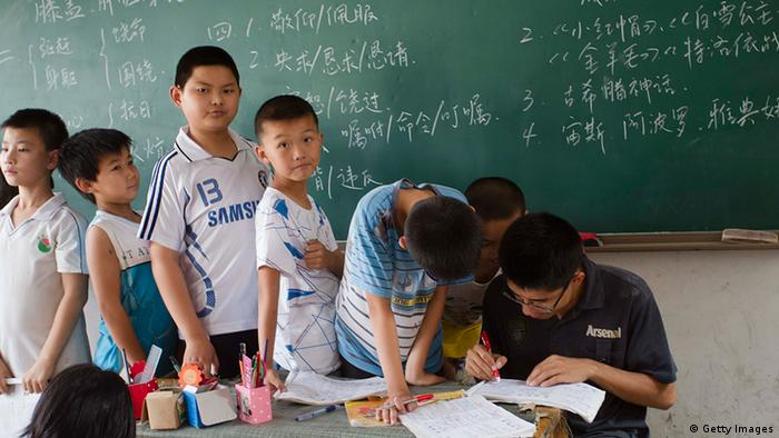 This picture taken on June 26, 2012, shows a group of children of migrant workers during classes at an illegal migrant school which has been ordered to close in Beijing, resulting in the children having to be sent back home to their provinces. Under China's complex residency laws, most migrant workers remain registered in their native towns or villages and do not qualify for the all-important hukou, or household registration permit, in the city where they live and without this document their children do not qualify for places in public schools, making the unregistered fee-paying migrant schools their only option. CHINA OUT AFP PHOTO (Photo credit should read STR/AFP/GettyImages) Quelle: Fars