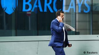 A city worker passes a Barclays bank branch in Canary Wharf, east London (photo: Olivia Harris / Reuters)