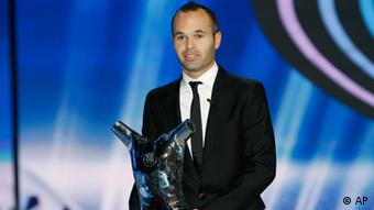 The best soccer player of the year, FC Barcelone's Spanish midfielder Andres Iniesta, holds his trophy during the UEFA Champions League draw, at the Grimaldi Forum, in Monaco, Thursday, Aug. 30, 2012.