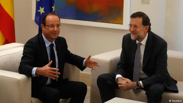 Spanish Prime Minister Mariano Rajoy (R) and French President Francois Hollande speak before their meeting at the Moncloa Palace in Madrid, August 30, 2012.