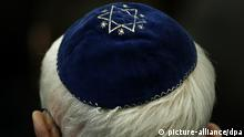 Foto: A man wears a kippah with a star sewn on the top(Foto: picture-alliance/dpa)