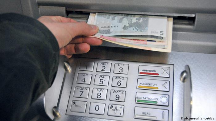 A person's hand takes money out of an ATM Photo: Uwe Zucchi dpa +++(c) dpa - Bildfunk+++