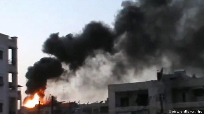 A grab from a handout video made available by Shaam News network on Sept. 1, 2012, shows a building on fire after a shelling in the city of Aleppo