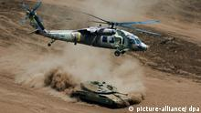 An Israeli helicopter flies over an army tank churning up dust traveling on a road in the stategic Golan Heights during a brigade-size exercise on 14 August 2008. The Israeli army uses the Golan Heights, captured from Syria in the 1967 Six Day War, extensively for armoured military exercises. EPA/JIM HOLLANDER +++(c) dpa - Bildfunk+++