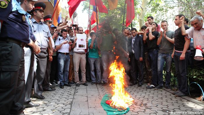 Protesters burn a flag in front of the Hungarian consulate during a rally in Yerevan, Armenia