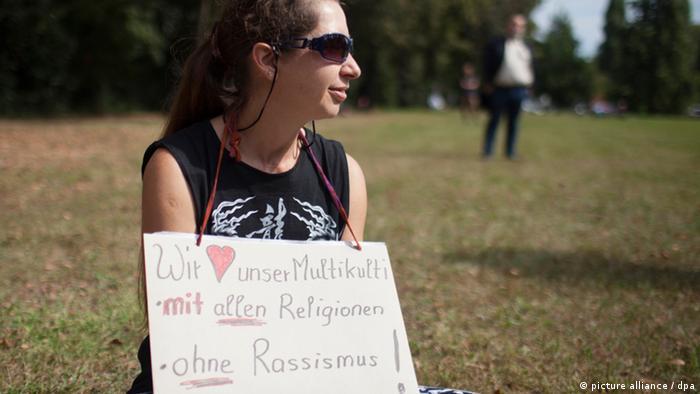 Eine Frau trägt ein Schild mit der Aufschrift: Wir lieben unser Multikulti - mit allen Religionen - ohne Rassismus! (Foto: dpa)