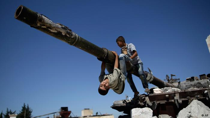 A boy looks back while he and another boy play on a Syrian military tank, (AP Photo/Muhammed Muheisen)