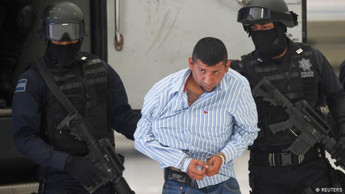 Federal police officers escort suspect David Rosales Guzman alias El Comandante Diablo as he is presented to the media during a news conference at the federal police headquarters in Mexico City