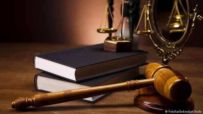 На столе лежат книги, судейский молоток и весы - символ правосудия
