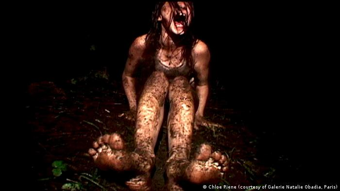 Chloe Pienes writhes around in mud in her video Blackmouth from 2004 at the new exhibition Fools. Artists. Saints. Masters of Chaos at the Bundeskunsthalle in Bonn. )