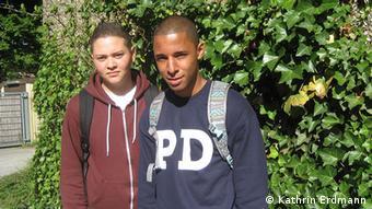 Dva mladića stoje u parku ispred drveta