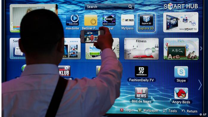 A man takes a picture with his cell phone in front of a smart TV at the IFA consumer electronics fair in Berlin, Germany, Friday, Aug. 31, 2012. (Foto:Michael Sohn/AP/dapd)