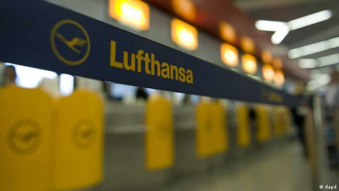 An temporary barrier at an airport with Lufthansa written on it.