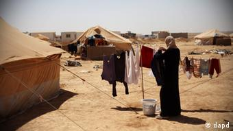 A Syrian refugee woman hangs her families clothes to dry at Zaatari Refugee Camp, in Mafraq, Jordan, Sunday, Sept. 2, 2012. (AP photo/Mohammad Hannon)