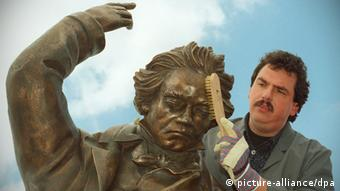 A man combing the hair of a bronze Beethoven