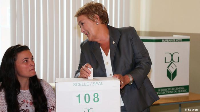 Parti Quebecois leader Pauline Marois smiles at a volunteer as she casts her vote
