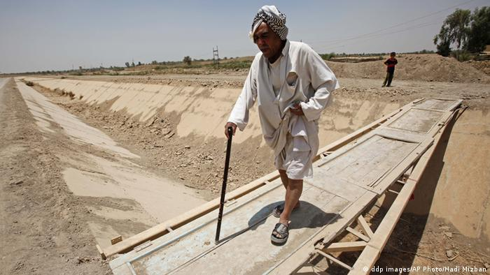 Man crossing a dry canal in Iraq during 2009 drought (Photo: ddp images/AP Photo/Hadi Mizban)