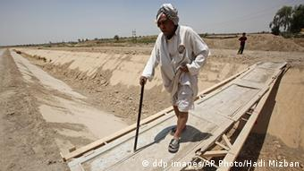 An old man crosses a dry canal in Latifiyah near Baghdad