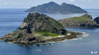 The survey ship Koyo Maru, left, chartered by Tokyo city officials, sails around Minamikojima, foreground, Kitakojima, middle right, and Uotsuri, background, the tiny islands in the East China Sea, called Senkaku in Japanese and Diaoyu in Chinese, Sunday, Sept. 2, 2012