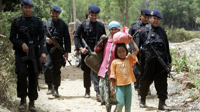 Indonesian shiite Musilim residents are escorted by police officers as they flee from Karanggayam village to a temporary shelter in Sampang, Madura island, East Java province, Indonesia, 27 August 2012 (Photo: EPA/FULLY HANDOKO +++(c) dpa - Bildfunk+++)