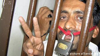 A Pakistani journalist flashes victory signs from inside the lockup of a police station after several journalists were arrested for protesting against the Emergency rule and curbs on media outside the Hyderabad Press Club in Hyderabad, Pakistan, 20 November 2007 (Photo:EPA/NADEEM KHAWER +++(c) dpa - Report+++)