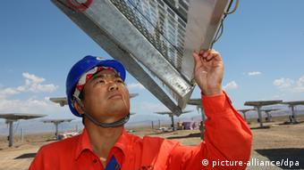 Chinese workers check and test solar panels at Fuguang photovoltaic power station in Hami city, northwest Chinas Xinjiang Uygur Autonomous Region, 6 August 2012. China, the biggest supplier of solar power panels, quadrupled a domestic installation goal for solar energy projects to 21 gigawatts by 2015 to help absorb the excess supply of panels and support prices. The target includes 1 gigawatt of solar-thermal power plants, said Shi Lishan, deputy director of the administrations renewable energy division. China had planned 5 gigawatts of capacity in the five years through 2015 and 20 gigawatts by 2020.