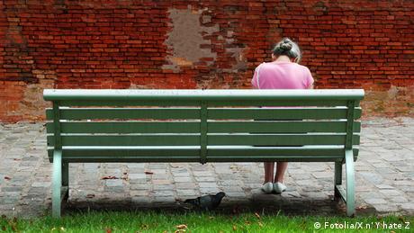 O femeie stă singură pe o bancă