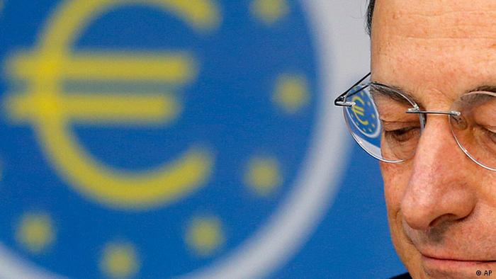 President of European Central Bank Mario Draghi listens to questions as the Euro logo is reflected in his glasses